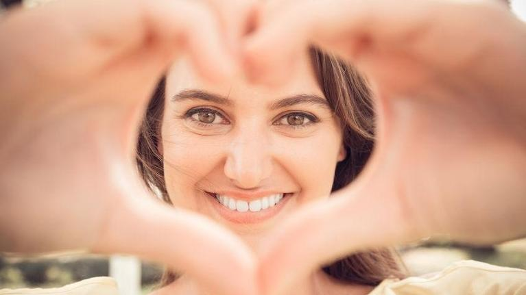 Woman smiling with hands in the shape of a heart