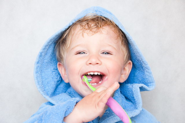 a child smiles and brushes their teeth | dentist chatswood nsw